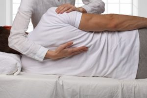 chiropractor adjusting male patients upper back