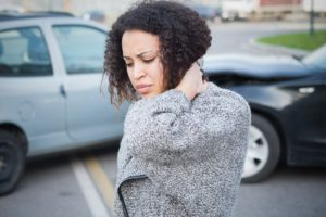 young woman holding her neck due too an auto accident injury
