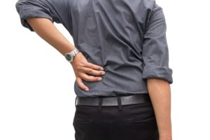 man holding his lower back due too pain