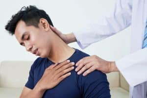 doctor stretching young male patients neck