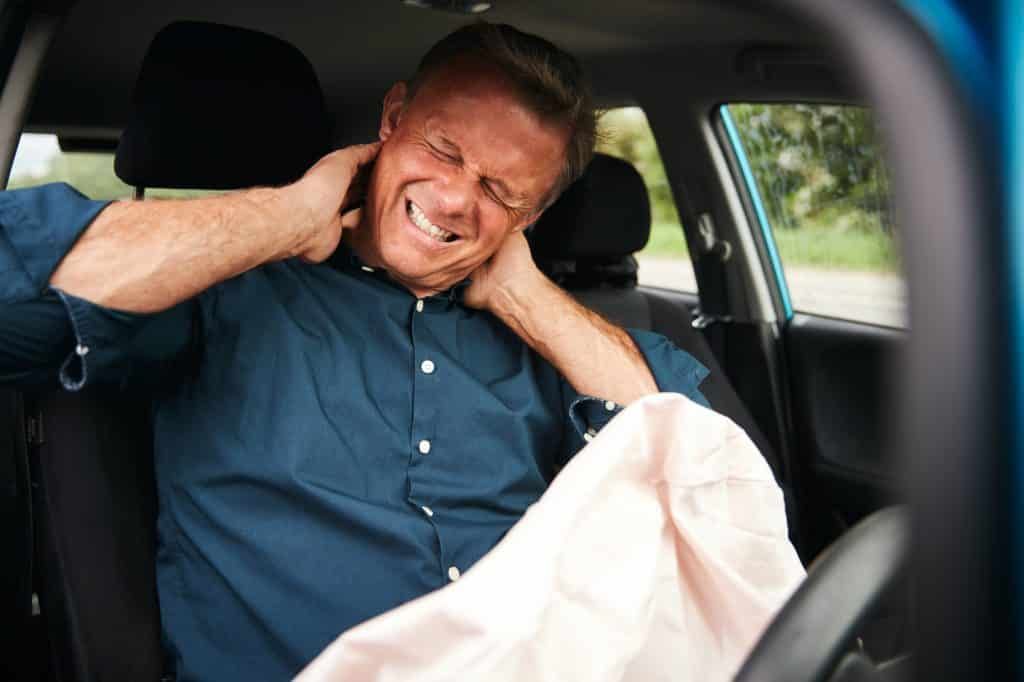 male driver holding his neck due to pain from a recent car crash
