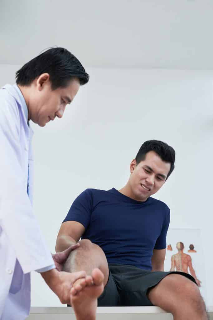 Doctor examining patient suffering from severe pain in his leg