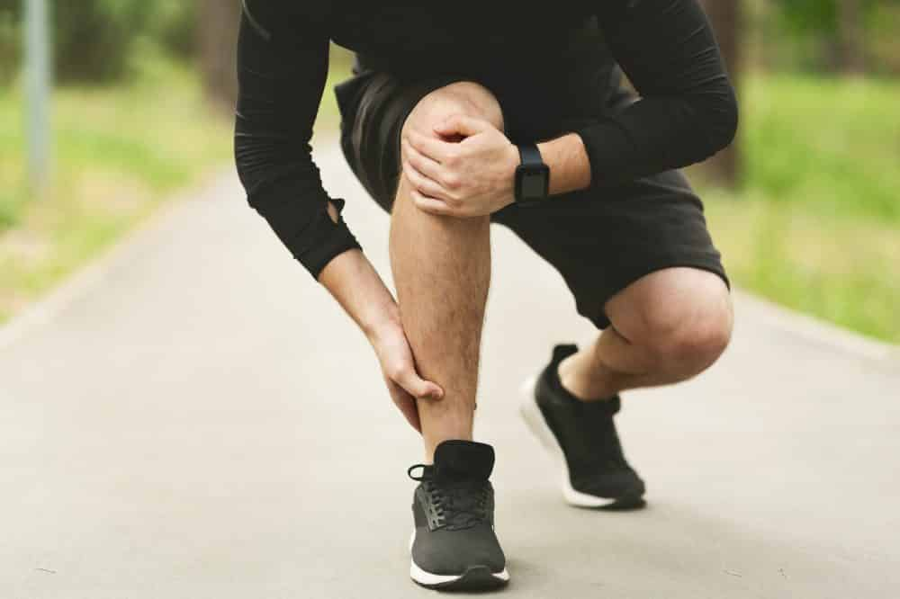 Young male runner is suffering from ankle