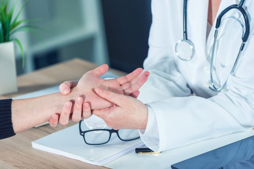female patient having her hand examined by a doctor