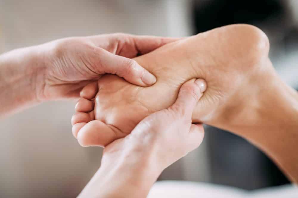 therapist massaging patients foot