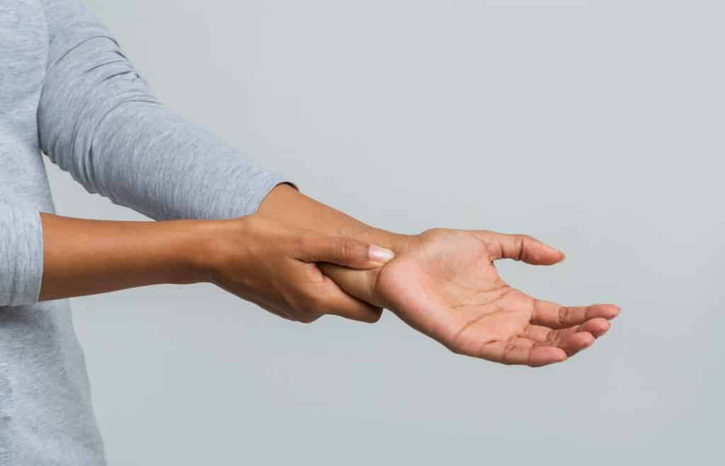 woman holding her hand due to pain