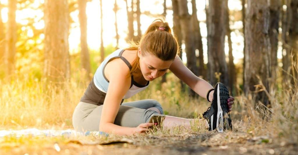 Woman exercising in the woods following recommended corrective exercises