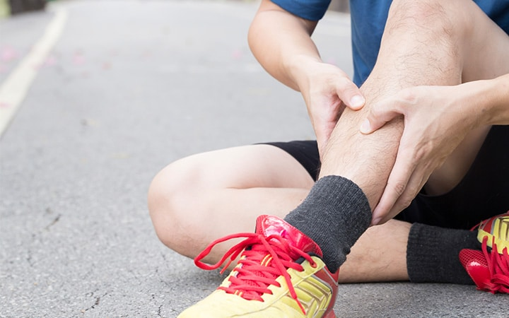 Runner sitting on the road suffering from leg pain.